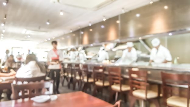 a blurry sushi bar, with chefs preparing sushi